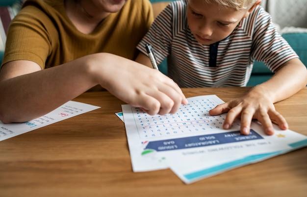 Сестра играет со своим младшим братом в поиск слов