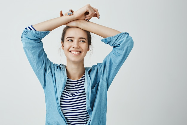 Sister recalled funny memories. indoor portrait of attractive creative woman holding crossed arms on forehead while smiling, looking aside, being happy, standing  in trendy outfit