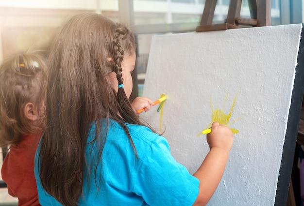 姉妹の子供たちは一緒にイーゼルのキャンバスにペイントします