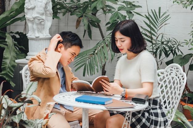 Сестра учит домашнее задание своему младшему брату, чувствуя себя смущенным