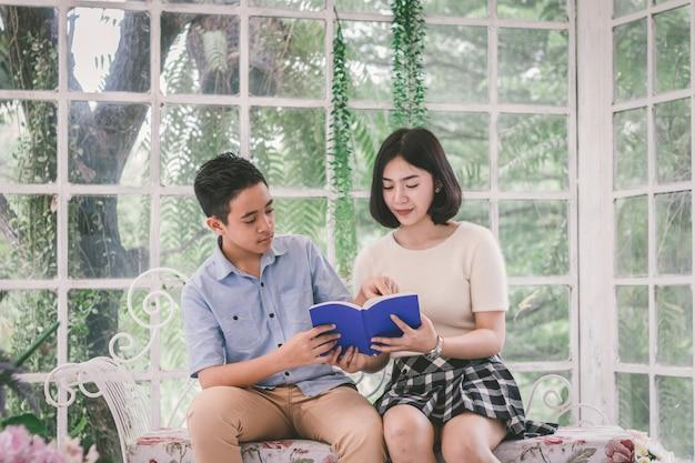 Сестра учит домашнее задание молодому брату в стеклянном доме