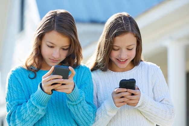 Sister twins having fun with technology smartphone