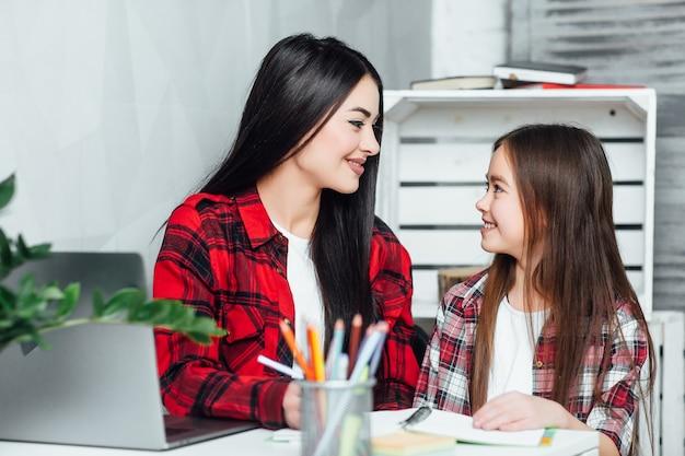 Сестра, что ты делаешь? две маленькие девочки делают домашнее задание дома
