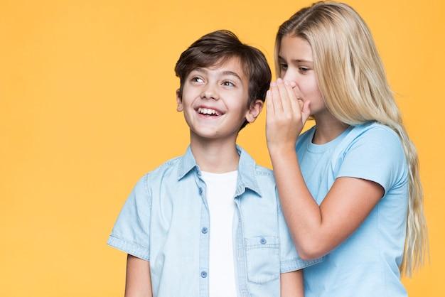 Sister whispering secret to little brother