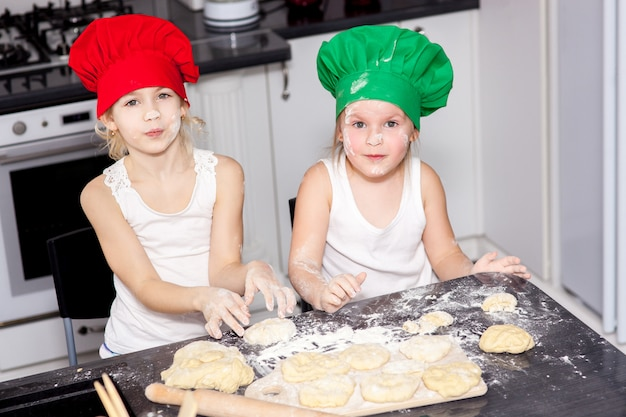 Sisters in bright cook hats baking together in a kitchen