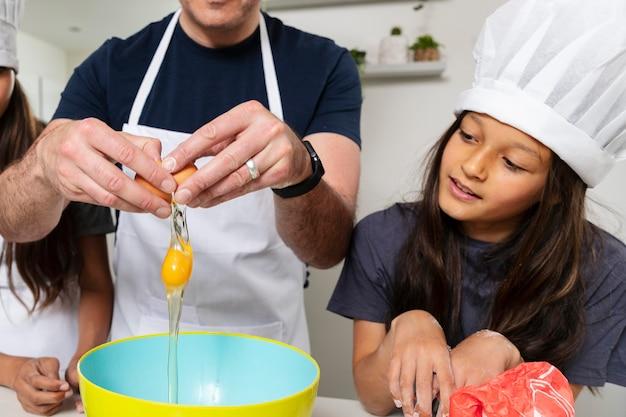 父親と一緒にキッチンで料理をする姉妹