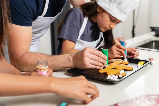 Sorelle che cucinano in cucina con il padre