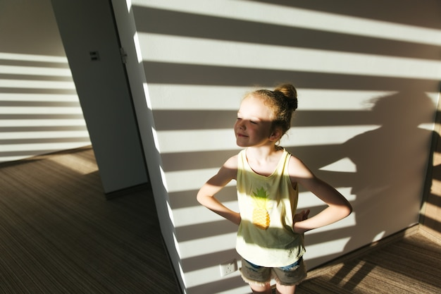 The sisters girls in the hallway of the hotel rejoices in the sun that shines through the blinds.