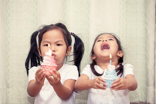 誕生日のカップケーキを一緒に吹く楽しみを持つ姉妹、ヴィンテージの色調