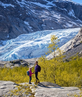 Sisters hiking at the mountains and the glacier nigardsbreen at the background