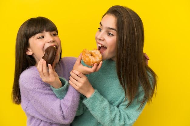 Сестры, держа пончик на изолированном фоне