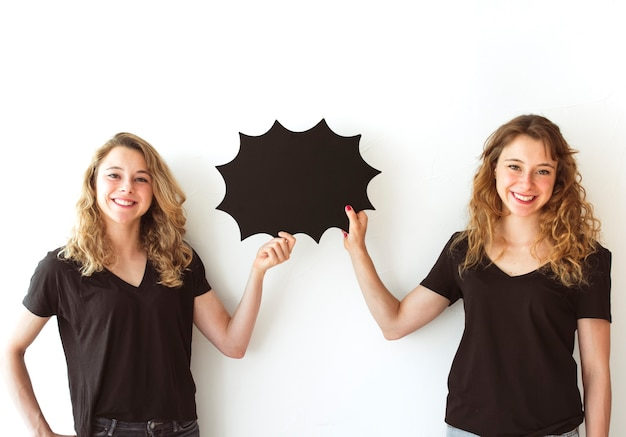 Sisters holding blank black speech bubble isolated over white background