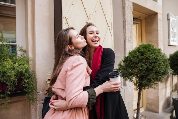 コートを着た姉妹が抱きしめています。