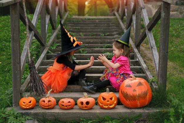 魔女の衣装を着た姉妹がハロウィンの階段に座っている
