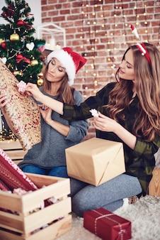 床にひざまずいてクリスマスの飾りを選ぶ姉妹