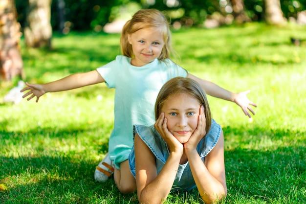 姉妹は芝生の上の公園に横たわっています。