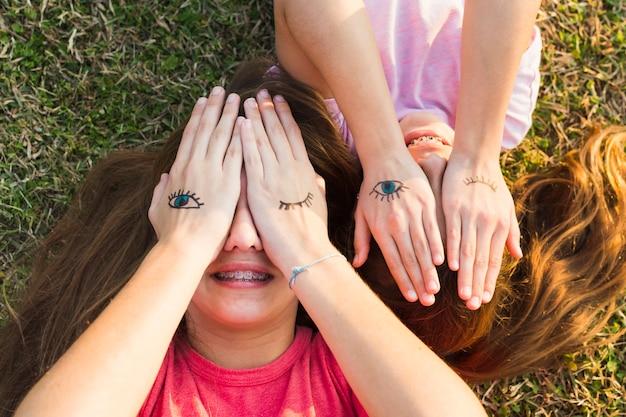 Sisters lying on green grass covering their eyes with tattoos on palm