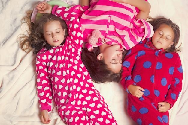 パジャマ姿の姉妹や友達がベッドで寝る