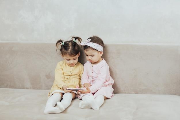 Сестры играют в игру на смартфоне