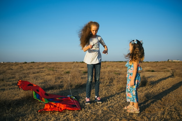 Sisters play with kite on the field