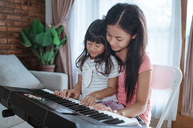 Sisters playing a piano instrument together