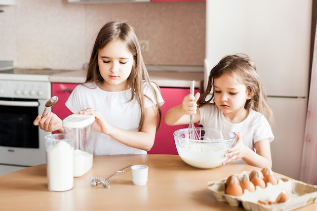 Sisters prepare breakfast, pastries, mix flour, milk, eggs, pancakes in a bowl, children help mother, family breakfast, cooking
