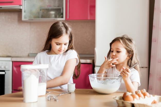자매는 아침 식사, 패스트리를 준비하고 밀가루, 우유, 계란, 그릇에 팬케이크를 섞고 아이들은 어머니, 가족 아침 식사, 요리를 도와줍니다.