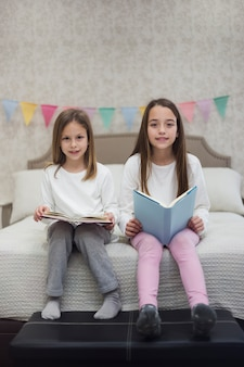 Sisters reading book together