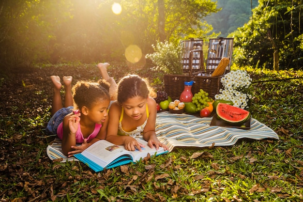 Sisters reading on picnic cloth