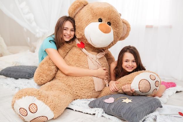 Сестры сидят и обнимают плюшевого медведя в игровой комнате