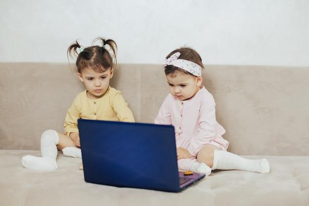 ソファに座ってノートパソコンで漫画を見る姉妹