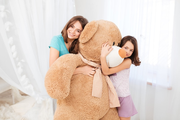 Сестры стоят и обнимают огромного плюшевого медведя