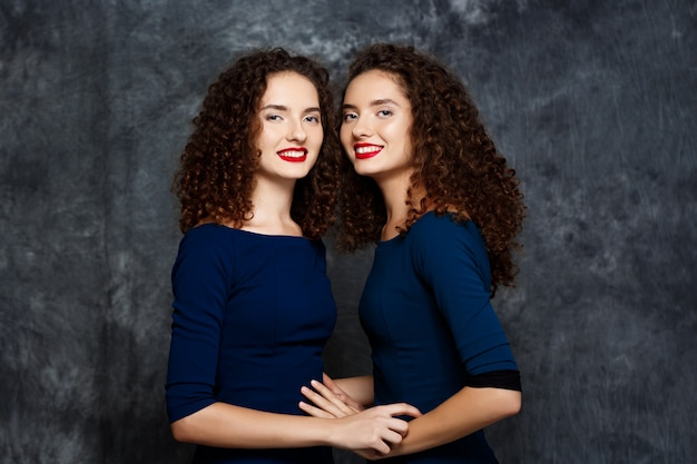 Sisters twins smiling on grey