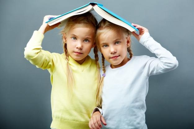 Sisters using an open book as an umbrella