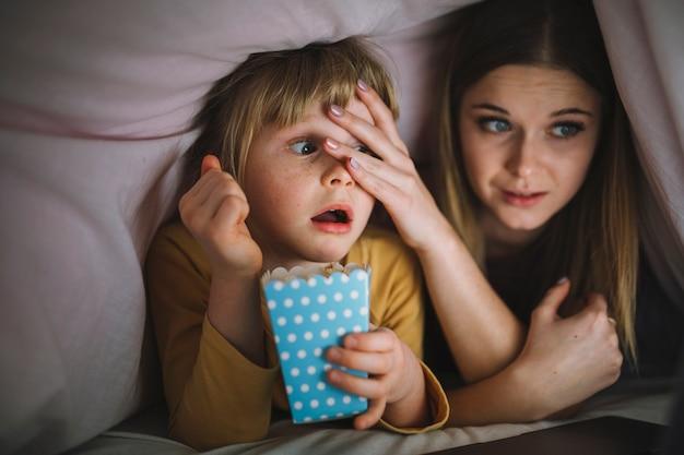 Sisters watching scary film under blanket