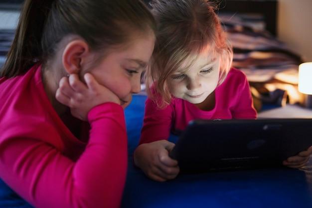 Сестры смотрят видео на столе