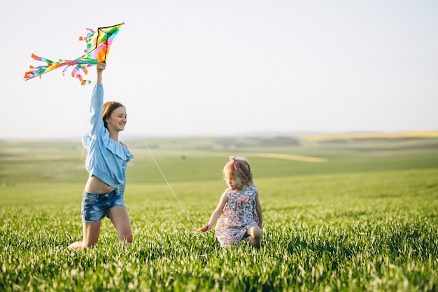 Sisters with kite in field