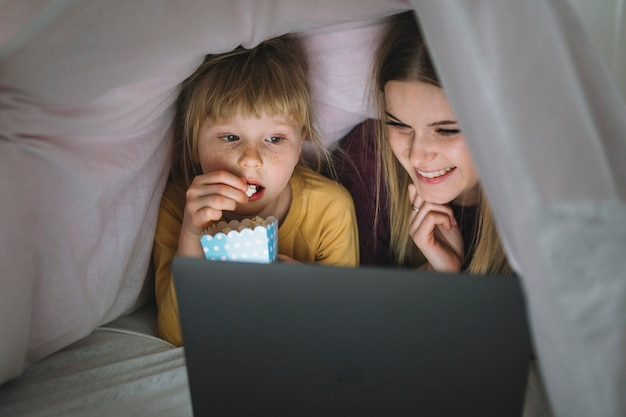Sisters with popcorn watching movie on tablet