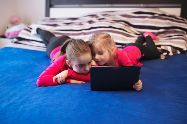 Sisters with tablet on bed