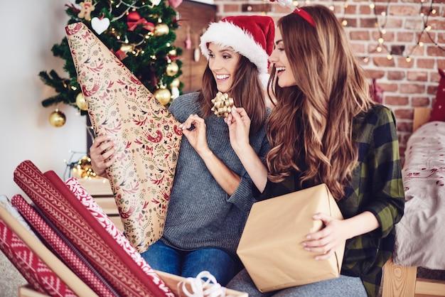 Sorelle che confezionano e decorano un regalo