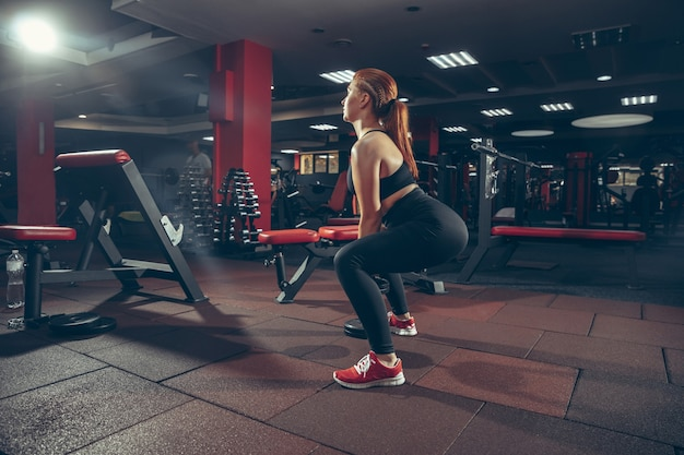 Sit up. young muscular caucasian woman practicing in gym with equipment. athletic female model exercising, training her lower body, working out with weight. wellness, healthy lifestyle, bodybuilding.