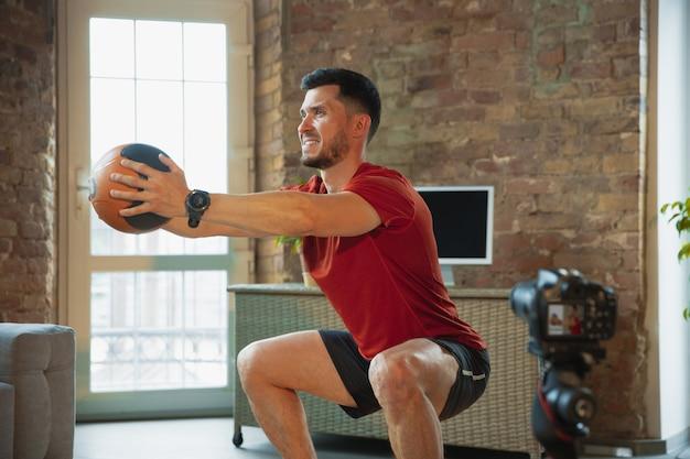 腹筋運動。コロナウイルスの発生の検疫中に自宅でトレーニングし、フィットネス、有酸素運動を行う若い白人男性。ビデオの録画またはオンラインストリーミング。ウェルネス、スポーツ、運動の概念。