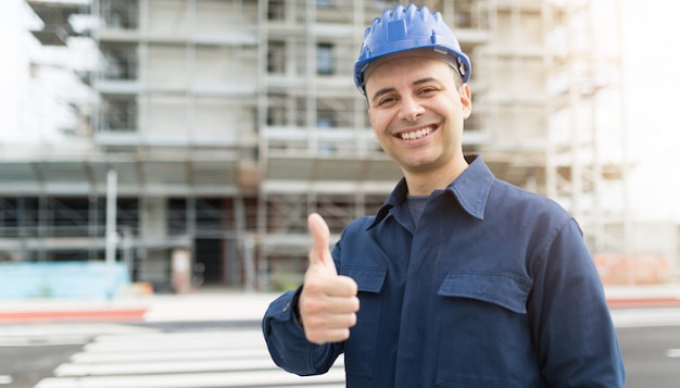Site manager giving thumbs up in front of a construction site