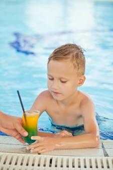 ホテルのスイミングプールでカクテルを飲むsititingで夏の暑い日にリラックスしたかわいい子供。子供と夏のコンセプトです。