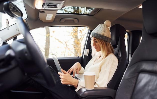 Сидит с ноутбуком и чашкой напитка. девушка совершила осеннюю поездку на машине. современный новый автомобиль в лесу.
