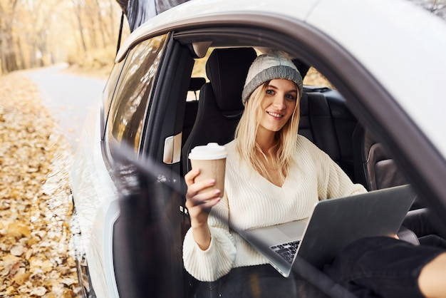 Sits with laptop and cup of drink. girl have autumn trip by car. modern brand new automobile in the forest.