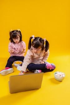 Сидя против ноутбука. любопытные маленькие девочки с генетическим заболеванием проводят время за ноутбуком в окружении тарелок с закусками