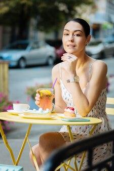 一人で座っています。屋外の黄色いカフェのテーブルに座って、レモネードを飲みながら彼女のあごに触れる穏やかなリラックスした女性