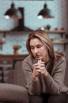 座って待っています。座って夫の帰宅を待つ金髪の主婦