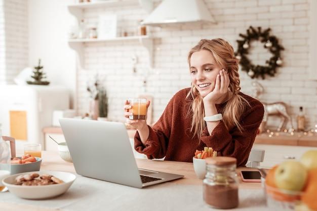 Сидя за столом. позитивная блондинка разговаривает по сети со своим ноутбуком, пьет стакан апельсинового сока